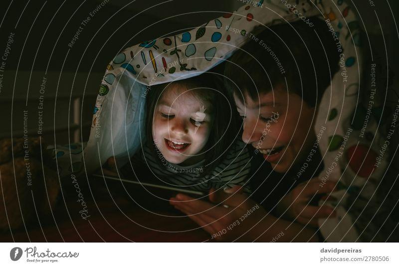 Brüder, die die Tafel im Dunkeln betrachten. Freude Glück Gesicht Spielen Schlafzimmer Kind Technik & Technologie Internet Mensch Junge Frau Erwachsene Mann