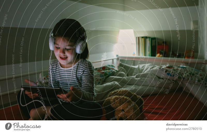 Mädchen mit Kopfhörern schaut auf das Tablett. Lifestyle Freude Glück schön Gesicht Spielen Lampe Schlafzimmer Kind Technik & Technologie Internet Mensch Frau
