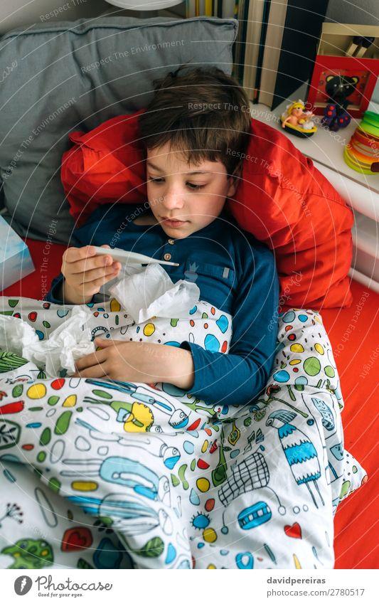 Kaltes Kind schaut auf das Thermometer. Lifestyle Krankheit Erholung Schlafzimmer Mensch Junge Mann Erwachsene Kindheit Buch Fluggerät Spielzeug authentisch