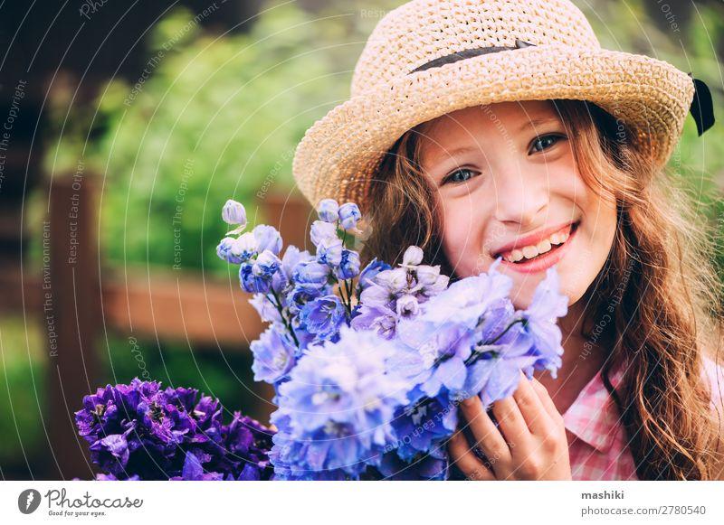 romantisches Porträt eines glücklichen Mädchens, das einen Strauß schöner blauer Rittersporn-Blumen aus dem Sommergarten pflückt Pflanze Blüte Kind spielen