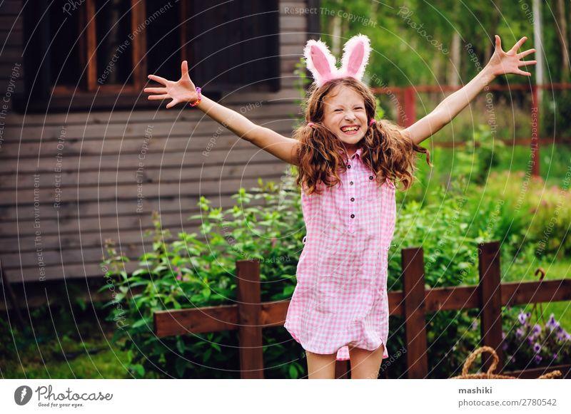 Osterporträt eines glücklichen Kindes Mädchen in Hasenohren Freude Spielen Haus Garten Feste & Feiern Ostern Familie & Verwandtschaft Kindheit Natur Gras Holz