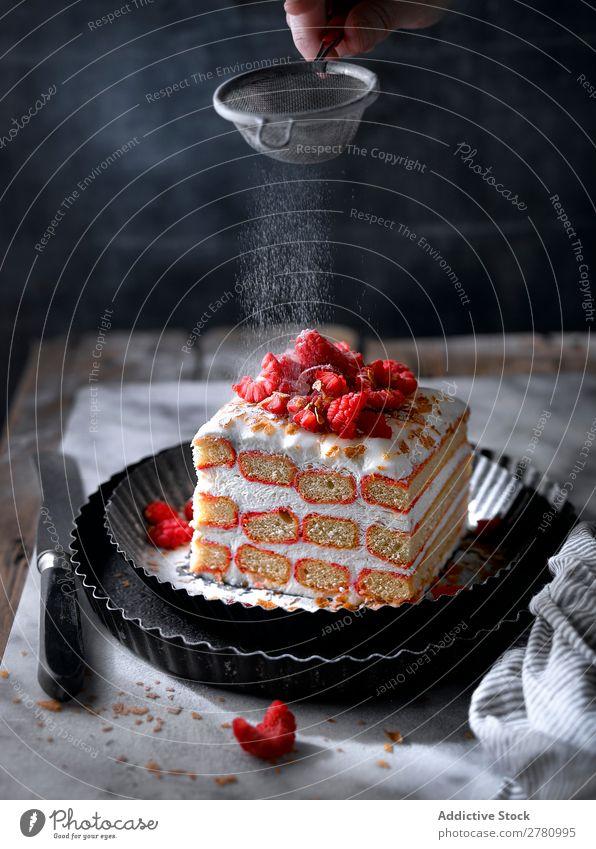 Pudern von süßen Beeren und Sahnekuchen Kuchen Himbeeren Pulver Zucker Dessert Lebensmittel geschmackvoll Essen zubereiten Tradition Genuss schön Konfekt frisch
