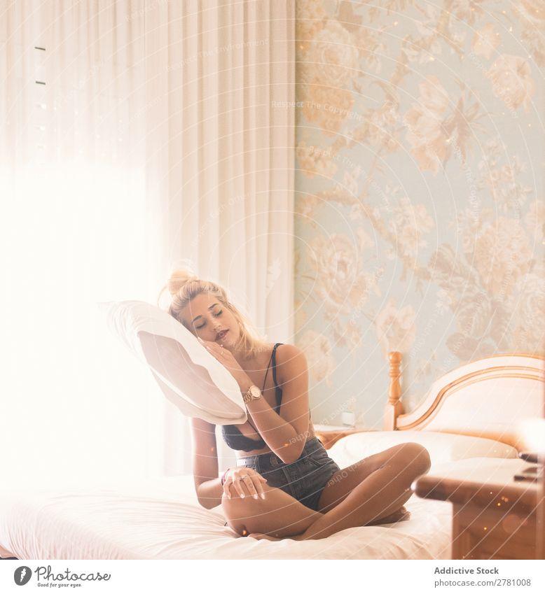 Hübsche blonde Frau gefaltet Kopf auf schwebendem Kissen Kopfkissen fliegen sitzen sexuell Erotik Jeansstoff BH Vorhänge Phantasie Augen geschlossen in der Luft