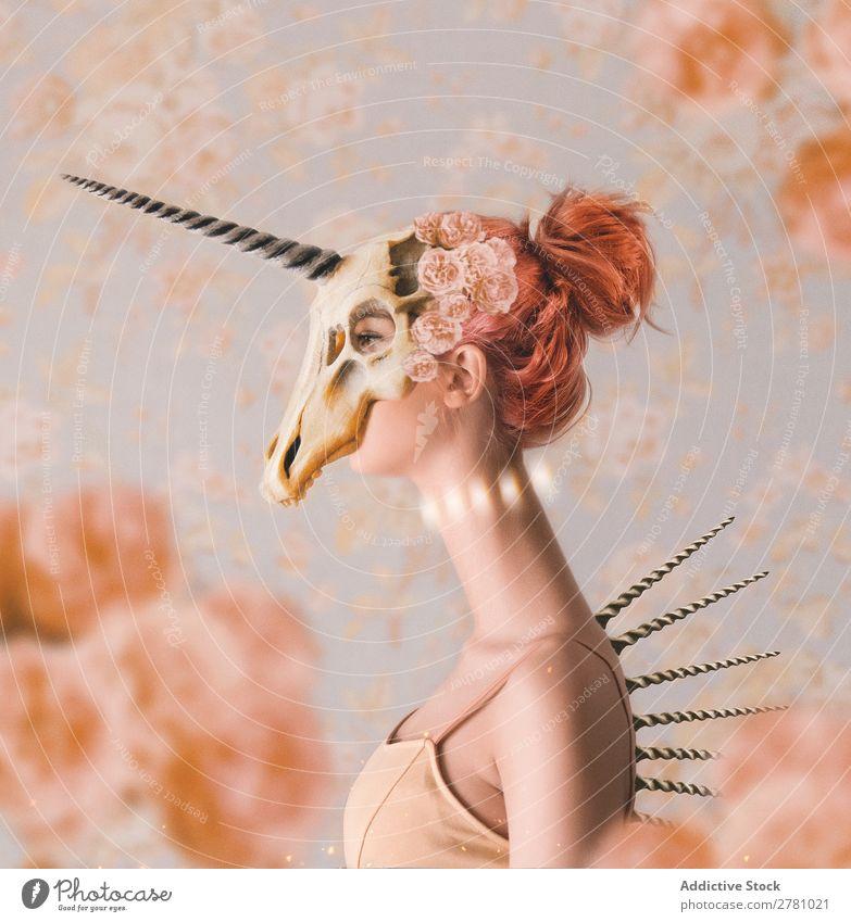 Frau mit langem Hals, die einen Einhornschädel auf dem Kopf trägt. Schädel Horntier verlängert attraktiv wunderschön anhaben Knochen Tier Hupe Tod Skelett