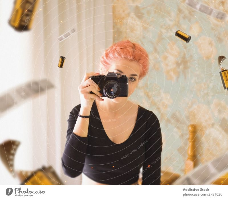 junges Mädchen mit rosa Haaren fotografiert mit Filmkamera Fotokamera Frau Fotografie Porträt Filmmaterial Blick in die Kamera horizontal abstrakt fliegen