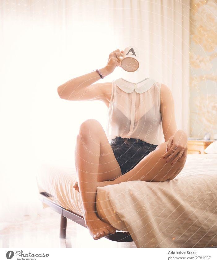 Kopflose Frau, die auf dem Bett nippt und Getränke trinkt. kopflos gesichtslos ohne Kopf Tasse Becher liquide Halt trinken Hand Arme Top weiß durchsichtig