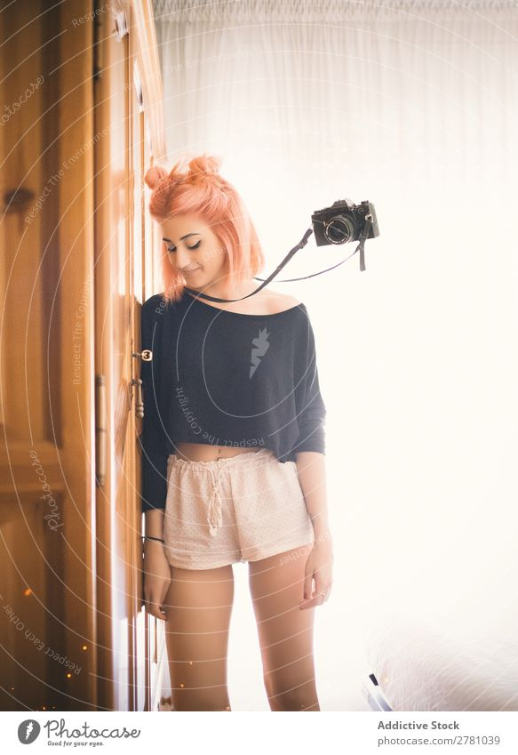 Filmkamera, die neben einer jungen rosa behaarten Frau fliegt. Fotokamera Porträt fliegen schweben altehrwürdig rosa Haare attraktiv wunderschön seltsam Entwurf