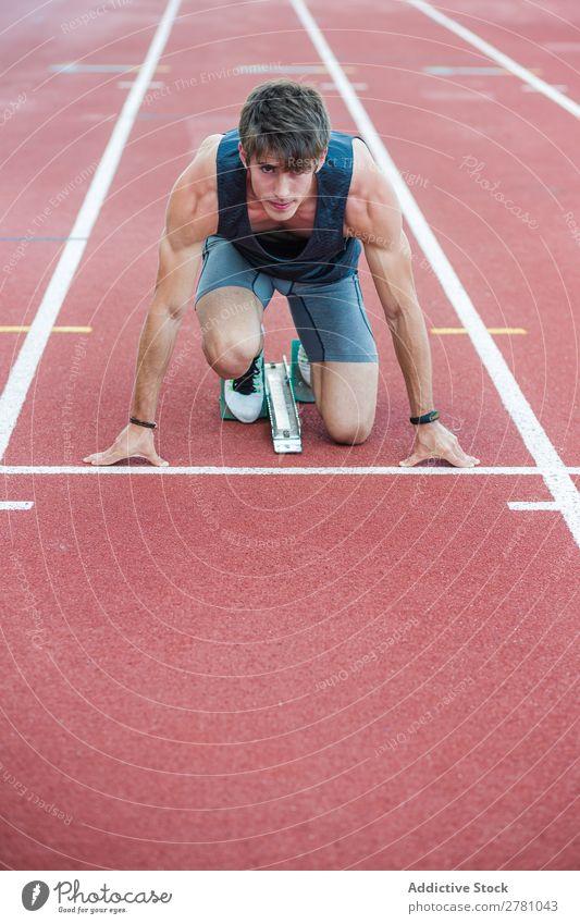Entschlossener Sportler beim Kauerstart Läufer Rennbahn Sprinter Biegen Stadion Erfolg Fitness üben Athlet muskulös Erwachsene Sportbekleidung sportlich
