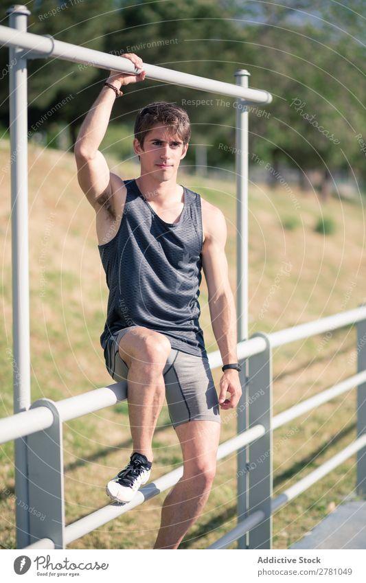 Gutaussehender Sportler posierend Mann Körperhaltung Stadion heiter ruhen Fitness üben Athlet muskulös Erholung Erwachsene Sprinter Pause Lächeln