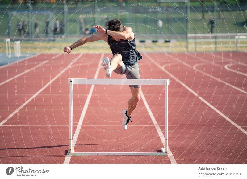 Mann springt über die Hürde rennen Rennbahn Athlet Bahn Tatkraft Konkurrenz wettbewerbsfähig Läufer Geschwindigkeit Feld Hürdenlauf konkurrieren Außenaufnahme