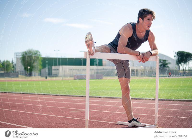 Mann beim Aufwärmen mit Planke strecken Stadion Sportler Körperhaltung beweglich Fitness üben Athlet Schiffsplanken stehen muskulös Gesundheitswesen Erwachsene