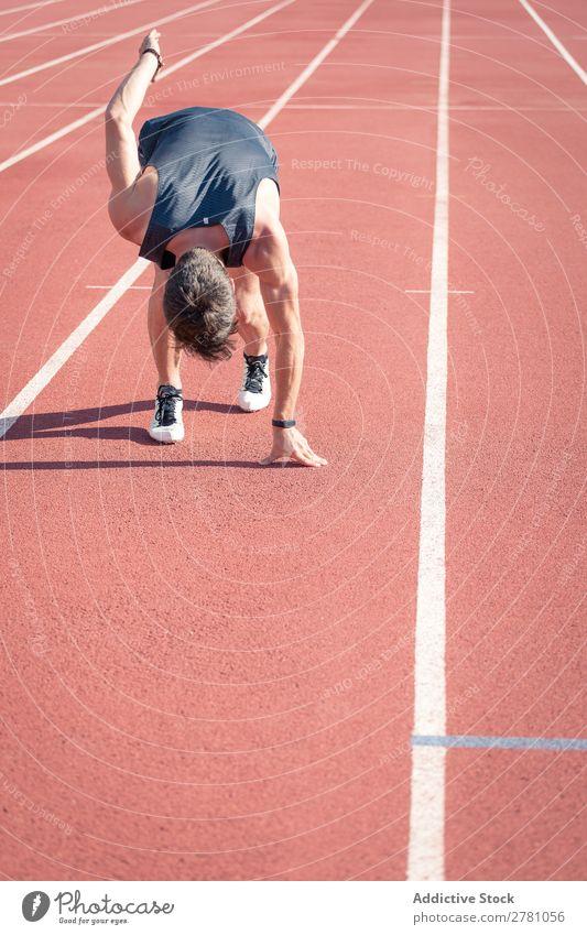 Mann in der Nähe der Planke im Stadion Sportler Läufer Rennbahn Kauerstart Sprinter Erfolg Biegen Fitness üben Athlet muskulös Erwachsene Sportbekleidung