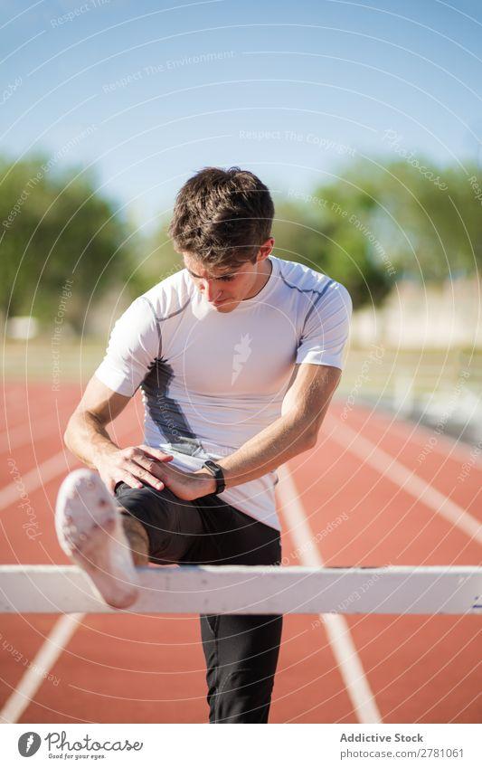 Junger Sportler streckt die Beine aus Mann strecken Stadion Körperhaltung beweglich Fitness üben Athlet muskulös Gesundheitswesen Erwachsene Sprinter sportlich