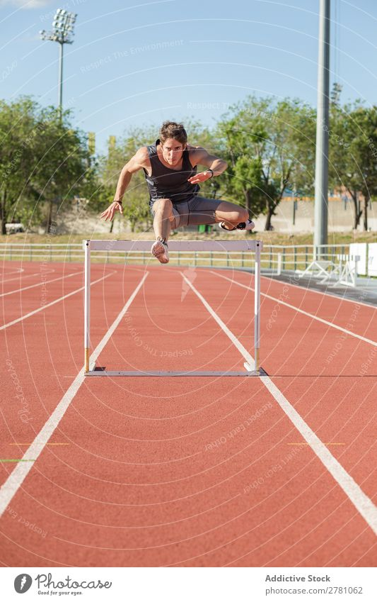 Sportler beim Springen über eine Hürde Körperhaltung Stadion stehen Fitness Athlet Rennbahn üben Schiffsplanken Mann muskulös Gesundheitswesen Erwachsene