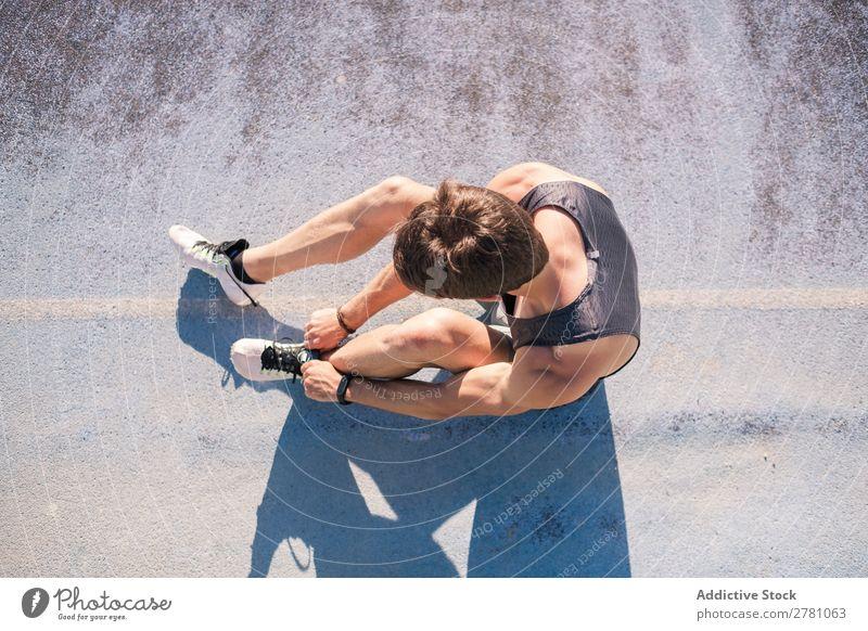 Sportler beim Schnürsenkelbinden Schuhbänder Rennbahn Beginn Krawatte Turnschuh Stadion Körperhaltung Fitness Läufer Athlet muskulös Gesundheitswesen Erwachsene