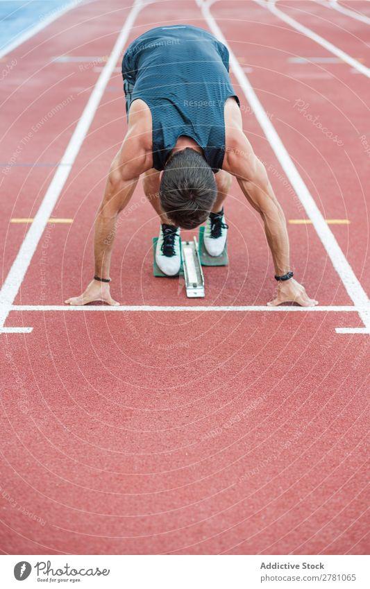Anonymer Sportler am Kauerstart Läufer Rennbahn Sprinter Stadion Erfolg Biegen Fitness üben Athlet muskulös Erwachsene Sportbekleidung sportlich Jugendliche