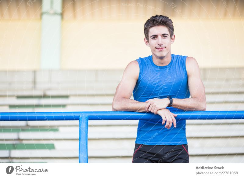 Junger Mann in Sportbekleidung, der sich auf einen Metallzaun lehnt und sich auf der Bühne posiert. Stadion sportlich Körperhaltung ruhen Sportler Fitness