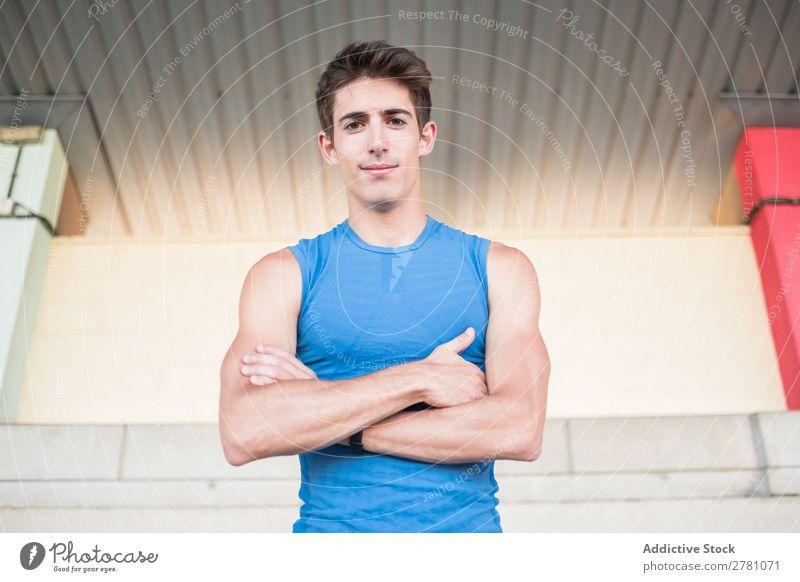 Muskulöser Mann, der vor der Kamera posiert. Stadion Körperhaltung ruhen Sportler Fitness die Hände gekreuzt üben Athlet muskulös Erholung Erwachsene Sprinter