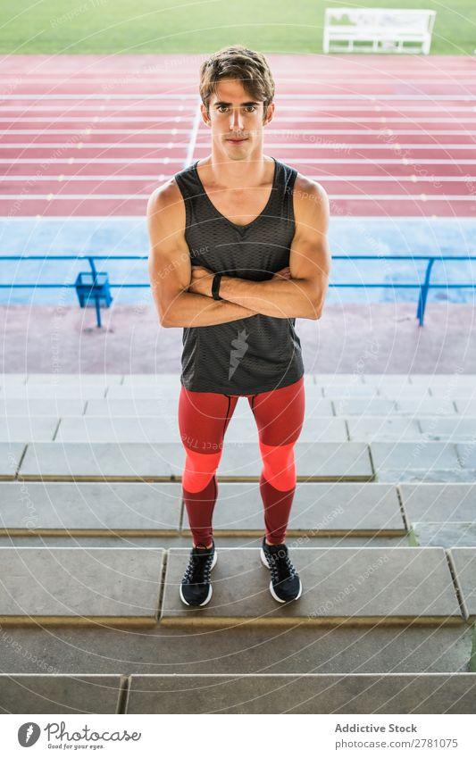Junger Sportler posiert im Stadion Mann Körperhaltung ruhen Fitness die Hände gekreuzt üben Athlet muskulös Erholung Erwachsene Sprinter Pause Sportbekleidung