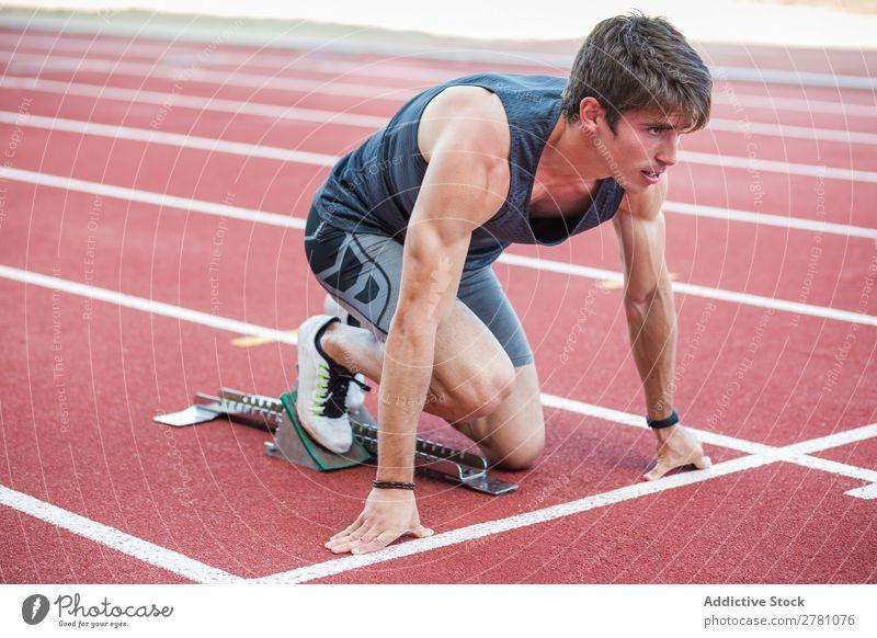 Sportler am Kauerstart Läufer Rennbahn Sprinter Stadion Biegen Fitness üben Athlet muskulös Erwachsene Sportbekleidung sportlich Jugendliche Außenaufnahme