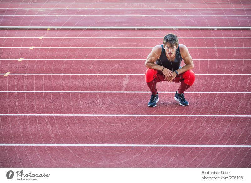 Sportler auf der Rennstrecke sitzend Mann Rennbahn ruhen Körperhaltung Kniebeuge Fitness üben Athlet muskulös Erholung Erwachsene Stadion Sprinter Pause