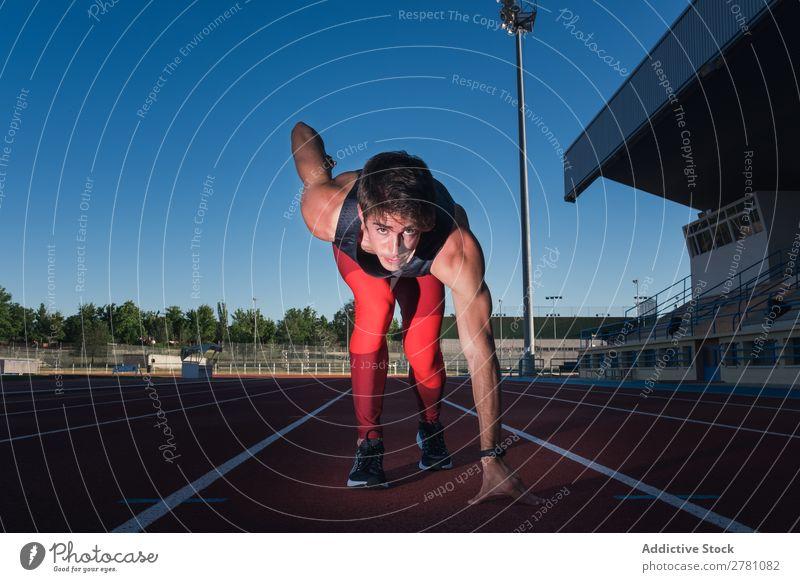 Junger männlicher Sprinter bereit zum Laufen Mann Kauerstart Rennbahn Konzentration Stadion sportlich Fitness Sommer Athlet Sport Erwachsene Sportbekleidung