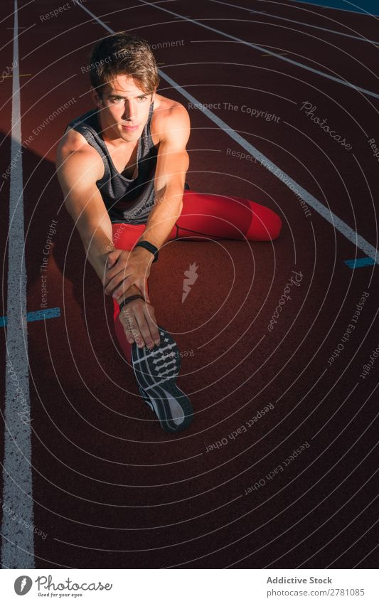 Sportler streckt die Beine im Stadion aus strecken Rennbahn Fitness üben Athlet muskulös Erwachsene Sportbekleidung sportlich Jugendliche Sprinter Außenaufnahme