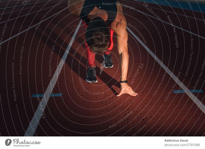 Mann in der Hocke Start Kauerstart Rennbahn Konzentration Stadion sportlich Fitness Sommer Sprinter Athlet Sport Erwachsene Sportbekleidung Bahn Läufer hockend