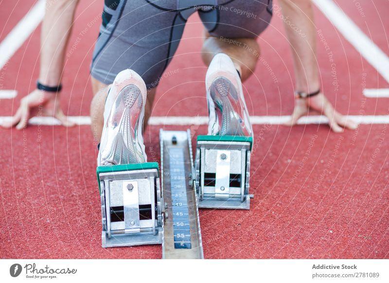 Mann verwendet Startblock zum Laufen Sportler Rennbahn Kauerstart Sprinter Sprungblock Stadion Erfolg Fitness üben Athlet muskulös Erwachsene Sportbekleidung 2