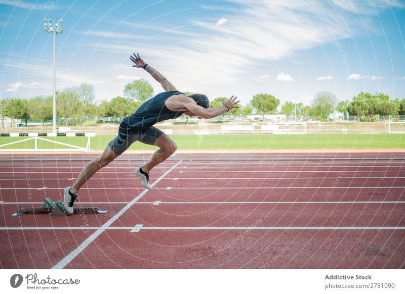 Seitenansicht des männlichen Sprinters Sportler Läufer Rennbahn Kauerstart Stadion Erfolg Fitness üben Athlet muskulös Erwachsene Sportbekleidung sportlich
