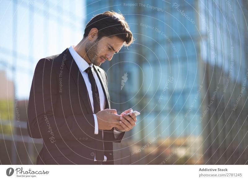 Eleganter junger Geschäftsmann auf der Straße mit dem Handy Mann Business Mode gutaussehend Jugendliche Blick Model Mensch Hintergrundbild Anzug modern