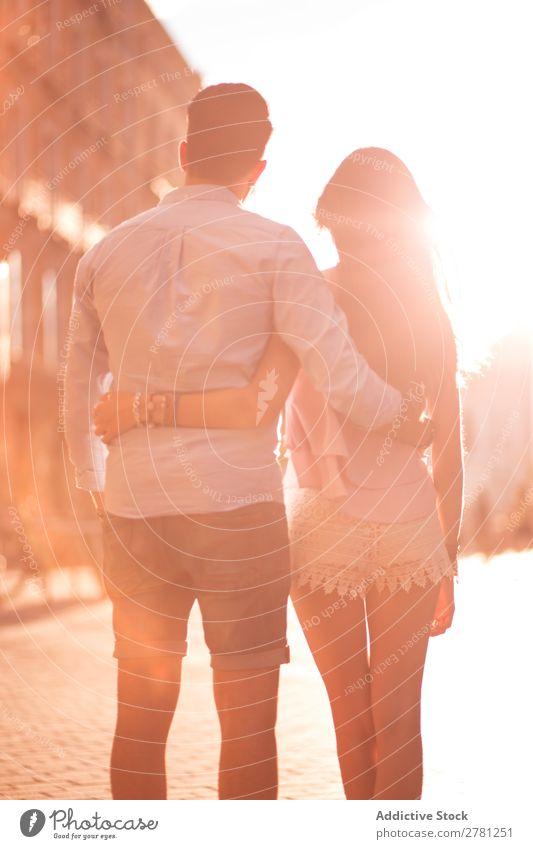 Nicht erkennbares umarmendes Paar in der sonnigen Straße Umarmen Rückansicht Sonnenlicht hell unkenntlich laufen stehen beobachten vertikal Heck Unschärfe