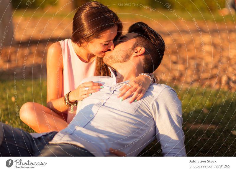 Bartiger Freund, der auf Gras liegt, während er seine Freundin küsst. Paar Küssen Porträt Sonnenlicht Abend Park Angebot Liebe Vollbart sitzen Umarmen hell
