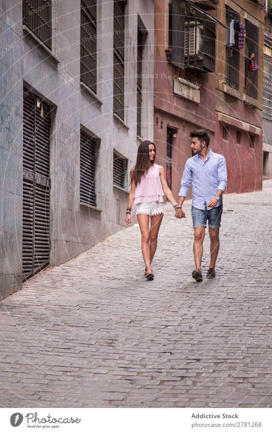 Junge Liebende, die auf der Straße spazieren gehen. Paar Glück Halt Hand laufen Frau Angesicht zu Angesicht Stil Angebot Mann Mensch Lifestyle romantisch