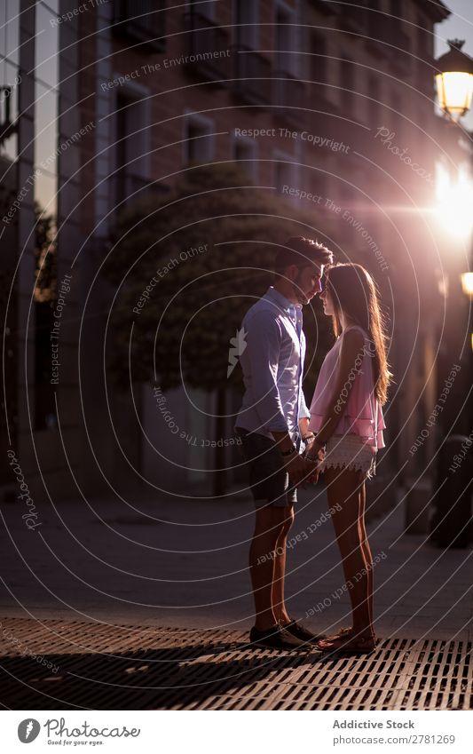 Junges Paar, das auf der Straße Händchen hält. Angebot Liebe Angesicht zu Angesicht Profil Sonnenlicht Jugendliche Zärtlichkeit stehen Stadt Freund Freundin