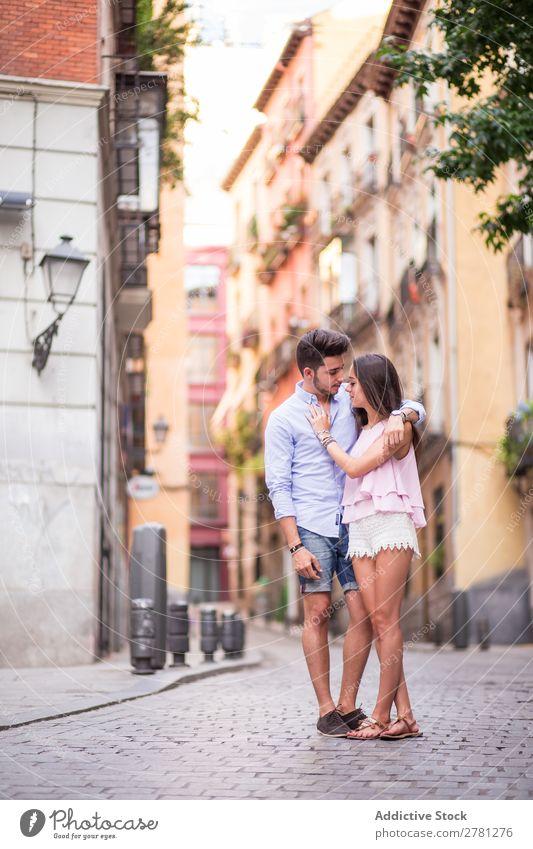Freund, der seine Freundin auf der Straße umarmt. Paar Romantik Porträt Angesicht zu Angesicht Gebäude Fassade Hintergrundbild lässig Ganzkörperaufnahme