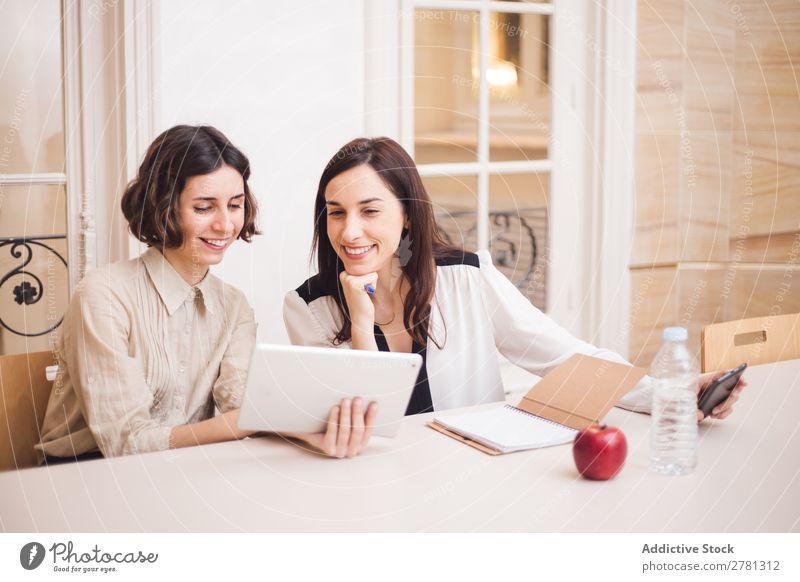 Junge Frauen, die auf das Tablett schauen und lächeln. Lächeln Tablet Computer Mitteilung Technik & Technologie heiter zeigen benutzend Business