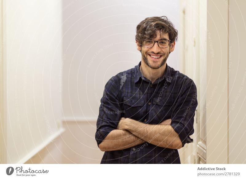 Junger lächelnder Mann im Hemd posierend Körperhaltung Lächeln heiter Porträt gestikulieren stehen Freundlichkeit verschränkte Arme positiv Blick in die Kamera