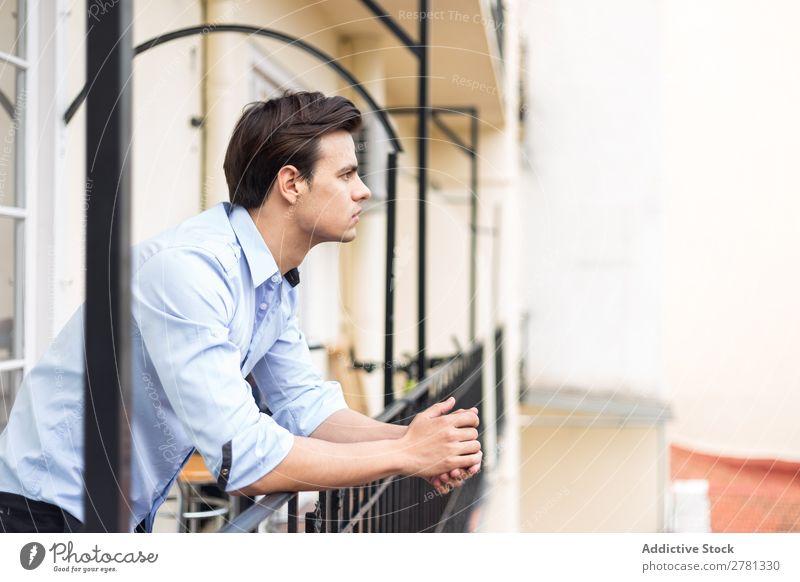 Junger seriöser Mann im blauen Hemd posierend ernst stehen Balkon Porträt gestikulieren Fürsorge besinnlich Körperhaltung Mensch 1 Jugendliche Erwachsene