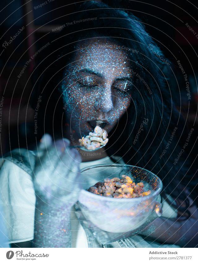 Frau mit Glitzer auf dem Gesicht beim Getreide essen Jugendliche hübsch Farbe malen Essen Müsli Lebensmittel Frühstück grau fluoreszierend leuchten erleuchten