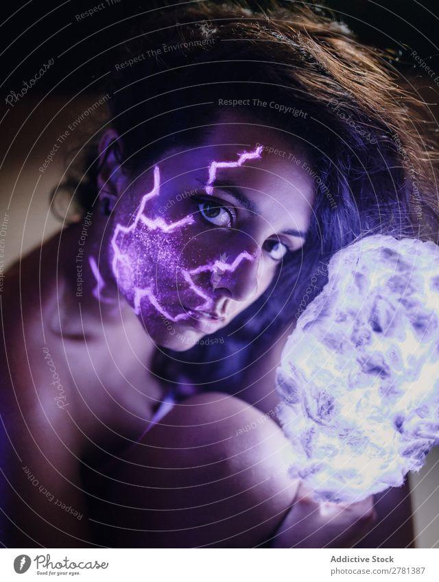 Frau mit leuchtender Farbe im Gesicht Jugendliche hübsch malen Feuer Leidenschaft fluoreszierend erleuchten Kunst neonfarbig Licht Mode mehrfarbig glühen