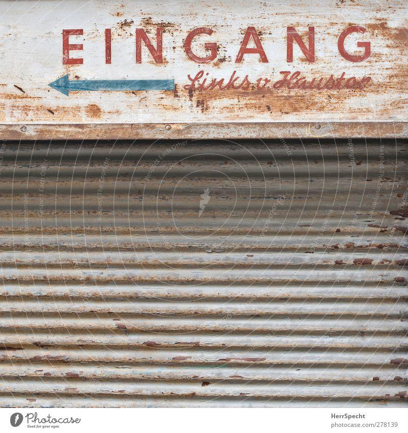 (K)Eingang Stadt Gebäude Fassade Metall Zeichen Schriftzeichen Hinweisschild Warnschild alt grau Pfeil links Rollladen geschlossen Rost Farbfoto Gedeckte Farben