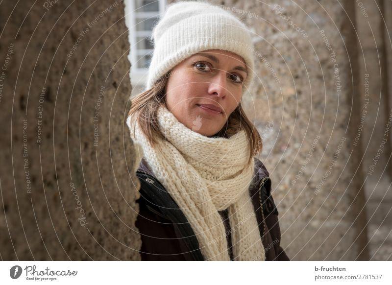 Portrait von Frau mit Schal und Mütze Erholung Erwachsene Kopf 1 Mensch Mauer Wand Mantel beobachten Blick stehen Freundlichkeit Fröhlichkeit Porträt Winter
