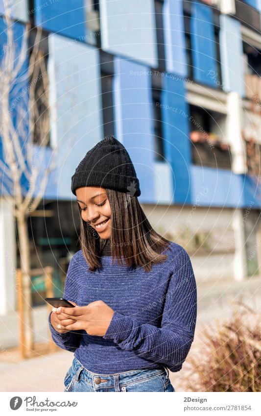 Glückliche Frau mit Hut in der City Street, während sie Technologie einsetzt. Stil schön Haare & Frisuren PDA Technik & Technologie Mensch feminin Junge Frau
