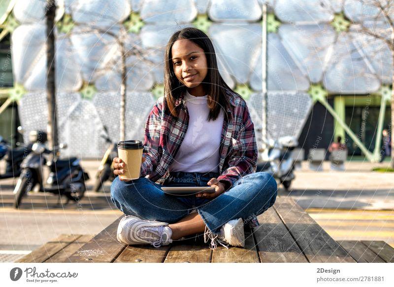 Junge schöne afroamerikanische Frau, die im Freien sitzt. Kaffee Tee Stil Glück Computer Technik & Technologie Internet Mensch feminin Junge Frau Jugendliche