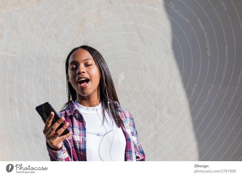 Vorderansicht einer jungen lächelnden Afroamerikanerin im Stehen Lifestyle Glück schön Entertainment Musik Telefon Mensch feminin Junge Frau Jugendliche