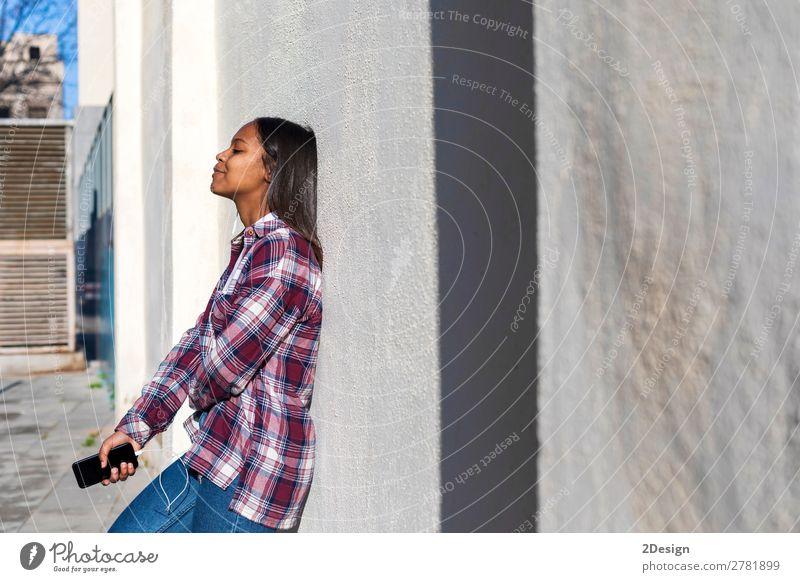 Schöne junge afroamerikanische Frau, die sich an eine weiße Wand lehnt. Lifestyle Stil schön Musik Telefon PDA Mensch feminin Junge Frau Jugendliche Erwachsene