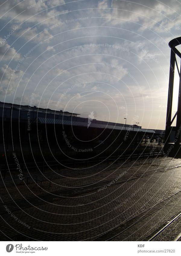 Sonnenuntergang im Industriegebiet Wolkenfetzen Kopfsteinpflaster Pflastersteine Fabrik Industrieanlage industriell Fabrikhalle Himmel Gleise Großmarkt