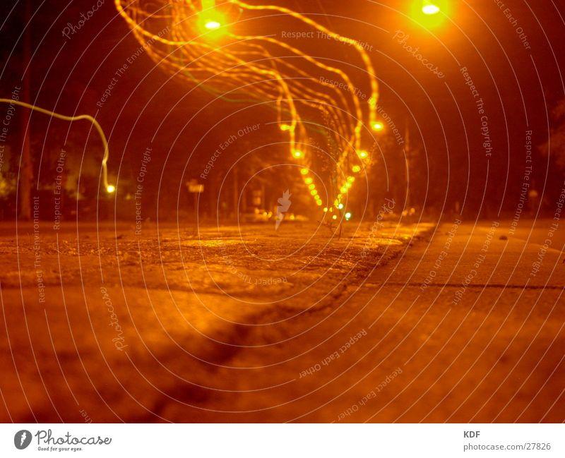 Einsames Pflänzchen Gleise Laterne Blitze Physik Einsamkeit Jungpflanze Kopfsteinpflaster Nacht Langzeitbelichtung dunkel Straße Wärme orange Bürgersteig Baum