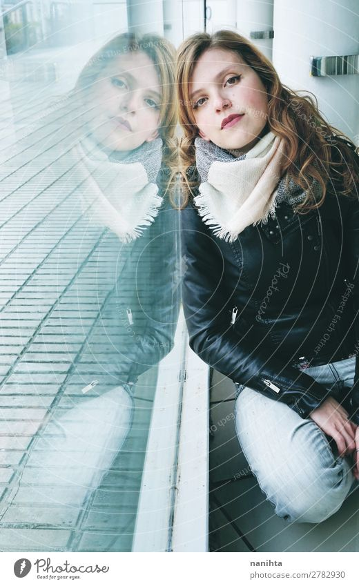 Junge schöne Frau, die sich in einem riesigen Fenster spiegelt. Lifestyle Leben ruhig Spiegel Mensch feminin Junge Frau Jugendliche Erwachsene 1 Straße Mode